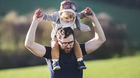 A father with his toddler son outside in green sunny spring nature, having fun.