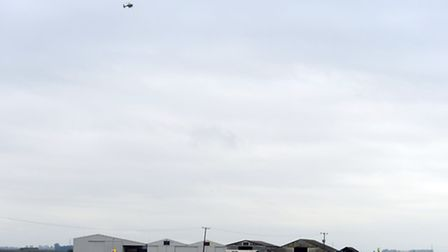 Emergency services at the scene of a plane crash at Shippea Hill. The police helicopter flying over