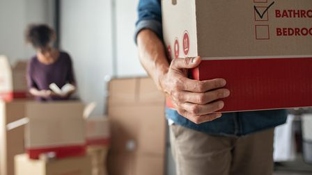 Closeup of man hand holding cardboard at new home. Young man unpacking boxes in new apartment. Man h
