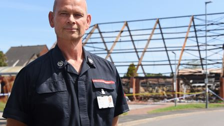 Jonathan Wilby, group manager, Norfolk Fire and Rescue, at the remaining shell of Budgens of Holt af