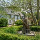 Large white farmhouse set behind lush green gardens with specimen trees and wooden sculptures