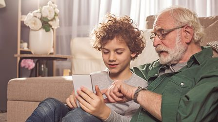 Grandfather helping his grandson with a tablet