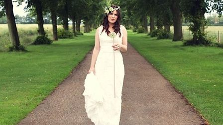 A bride in an avenue of trees at Kenton Hall Estate