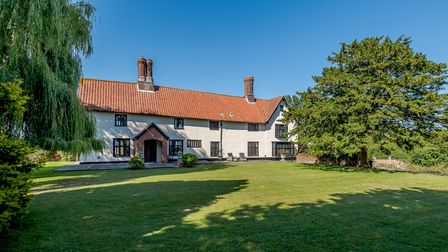 Large white listed farmhouse set back from huge grassy lawn with bright blue sky