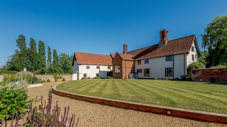 Large white brick-built farmhouse adjoining walled garden with manicured green lawns