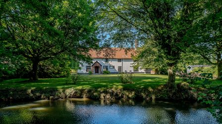 Huge white farmhouse viewed from across a private moat surrounded by trees