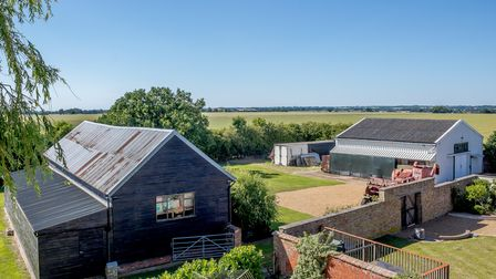 Aerial view of substantial farm outbuildings overlooking rolling fields under bright blue sky