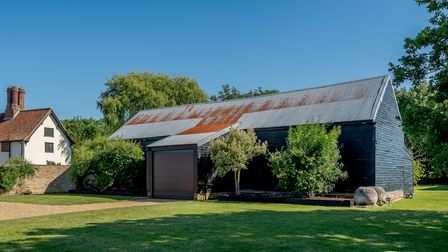 Large timber-framed outbuilding with metal roller door and shingle driveway