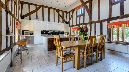Huge modern kitchen with vaulted ceiling, timber panelling, tiled floor and pine breakfast table