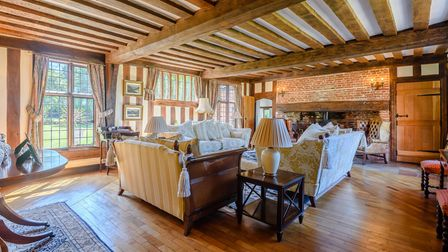 Huge living room with wooden floor, timber-beamed ceiling and brick-built hearth