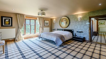 Huge double bedroom with plaid-effect floor, sash window, mirror above the bed and patterned wallpaper