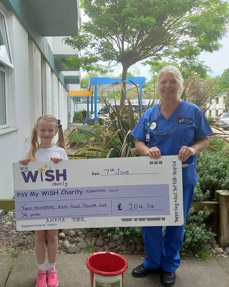 Anaiya Dyer hands over the cheque to the My WiSH charity