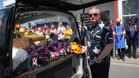 Tesco manager, Eric Keeler placing flowers into the hearse.