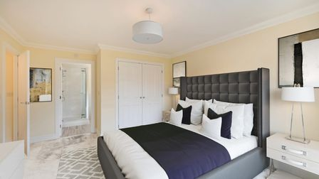 Large master bedroom with door opening into en suite, double bed, mirror and thick carpet