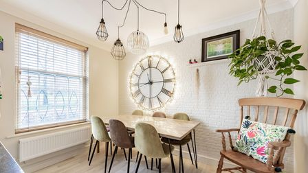 Corner of an open-plan kitchen with dining table to seat six against exposed brick wall painted white
