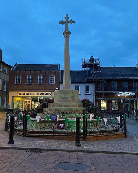 The war memorial in green bunting to honour St John's Day.
