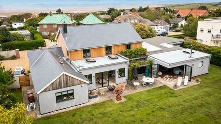 Aerial view of contemporary family home with large lawned south-facing garden