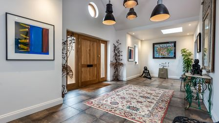 Large welcoming entrance hall with vaulted ceiling, oak door, tiled floor with rug and modern chandelier-style hanging lamps