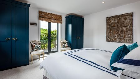 Large double bedroom with Juliet balcony, two floor-to-ceiling navy blue wardrobes