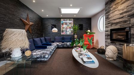 Sitting room with modern 'L'-shaped sofa, electric fire in modern chimney breast, oval coffee table