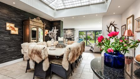 Luxury dining area with glass domed roof and white tiled floor with patio doors overlooking garden