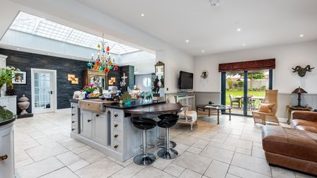 Light-filled open-plan living space with breakfast bar, seating area, patio doors leading to garden