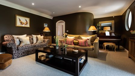 Dark and moody contemporary living room with two sofas, black coffee tables and unusual curved wall