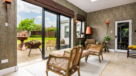 Seating area with rattan chairs and stool overlooking rear garden with open bi-fold doors
