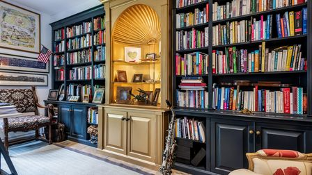 Built-in black bookcases with ornate Art-Deco style cabinet, colourful book spines and high white ceiling