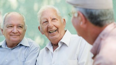 Active retirement, group of three old male friends talking and laughing on bench in public park. Pic