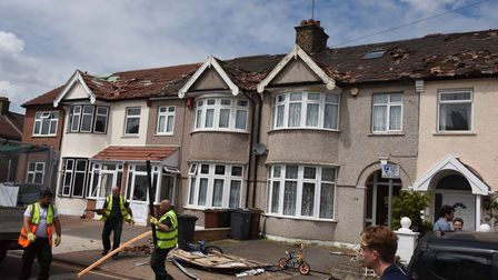 Council workers clearing debris in Wilmington Gardens, Barking, with damaged roofs clearly visible