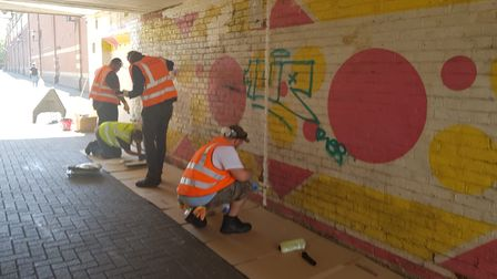People covering graffiti in St Awdry's Walk