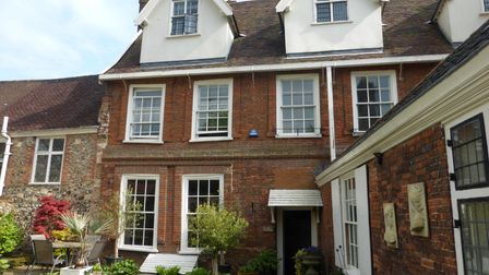 Three-storey brick-built period building with paved patio garden out the front