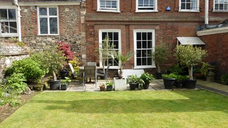 Well-kept lawn in front of a brick-built historic building with sash windows
