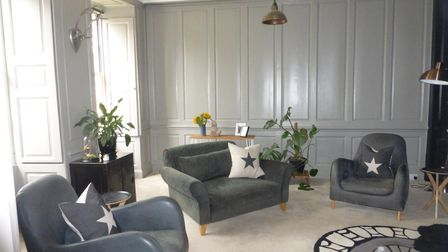 Panelled sitting room with pale grey walls, modern leather and suede armchairs and hanging pendant lamp