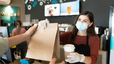 Young female staff giving parcel and coffee to customer at takeaway counter in coffee shop