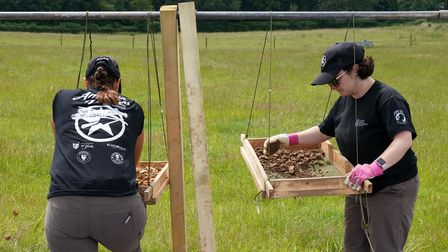 Archaeologists and American Defense POW/MIA Accounting Agency staff work to recover the remains of a