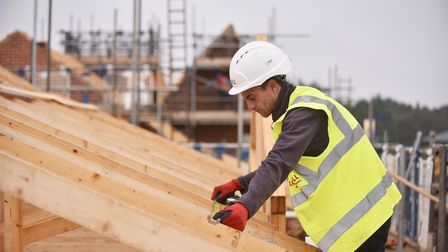 Workman with yellow fluorescent vest reading 'Lovell' and measuring roof timbers on a UK building site