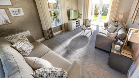 Inside the living room of a luxury show home with patio doors out to garden and two sofas