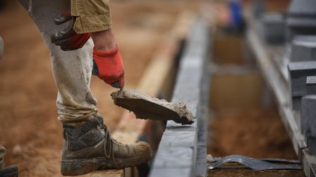 Close up of workman bending over to lay bricks with a red gloved hand and a trowel heaped with cement