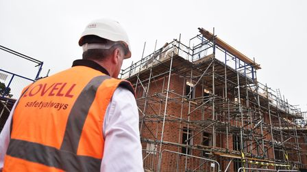 Back of construction manager with orange fluro vest reading 'Lovell' looking at brick new builds with scaffolding