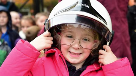 Paige Stimpson, 5, tries on the helmet as children from West Earlham Infant School learn about fire