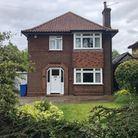 Detached brick-built period property with square bay window, single chimney and paved path to the front door