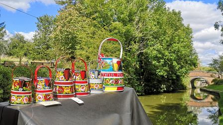 Kay paints traditional bucky cans for narrowboat decoration