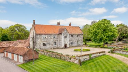 Large brick home with walled driveway, wide lawns and brick-built outbuildings including stables