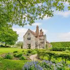Gable end of large flint country house set in beautiful luscious landscaped gardens