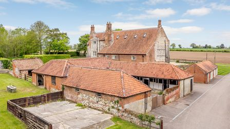 Brick and flint outbuildings, mostly stables and farm buildings, beside historic 16th century country house