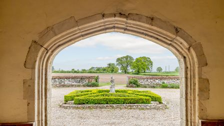 Curved stone doorway looking out to bright green parterre in centre of shingle driveway