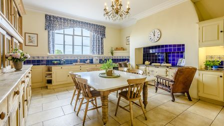Country style kitchen with cream-coloured Aga, wooden table and chairs and painted kitchen cupboards
