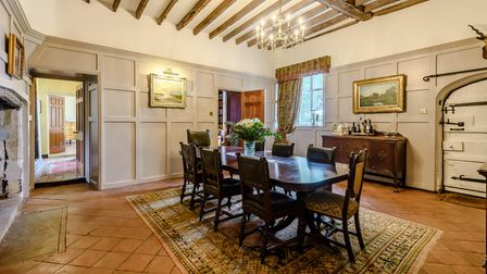 Panelled dining room with mahogany table, chairs, pantile floor and timber beamed high ceiling